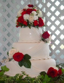 Stacked rolled fondant wedding cake with twists, drapes and fresh roses