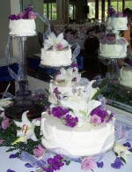 Spectacular 4-tiered wedding cake on crystal pillar system with colored fountain and fresh flowers