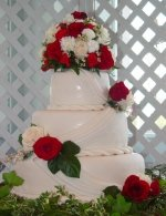 Rolled fondant weddding cake with drapes and roses.