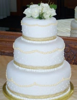 Stacked rolled fondant wedding cake with golden pearl details in buttercream