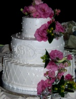 Stacked wedding cake with monogram and fresh flowers
