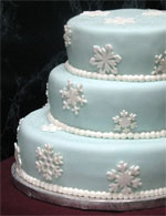 Small icy blue stacked fondant wedding cake with white snowflakes