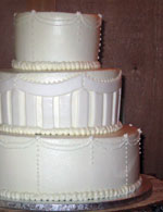 Stacked wedding cake in buttercream and rolled fondant.