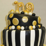 Whimsical graduation cake in black and gold rolled fondant.